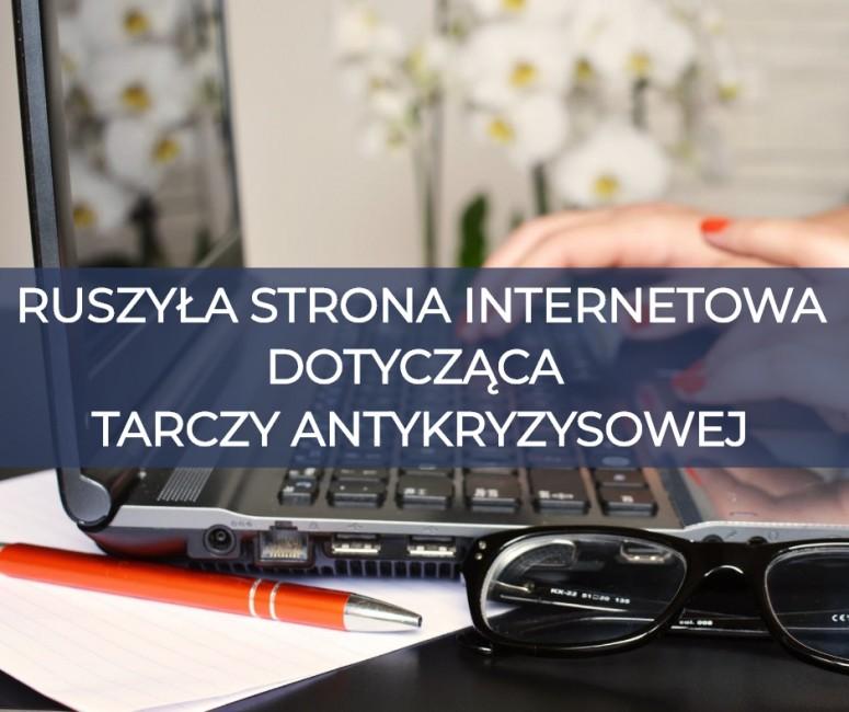 """obraz przedstawia napis """"Ruszyła strona internetowa dotycząca Tarczy Antykryzysowej"""" nałożony na zdjęcie komputera typu laptop, widoczne są ręce kobiety, jej okulary, długopis oraz notes"""