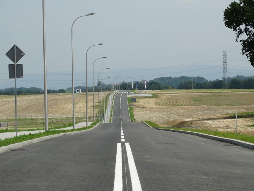 Zdjęcie przedstawia teren inwestycyjny do którego prowadzi droga publiczna. wzdłuż drogi ustawione są lampy oraz znaki drogowe.